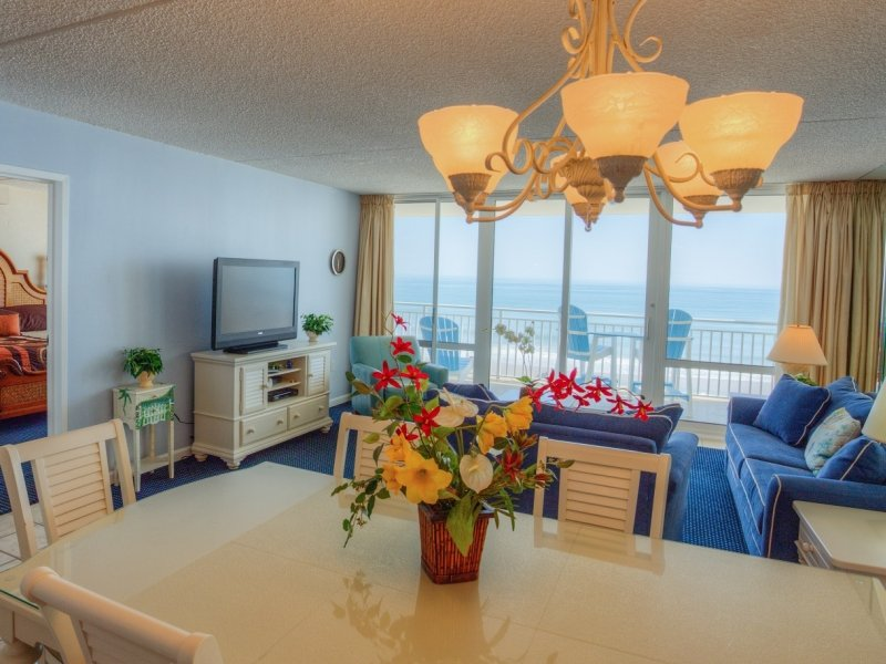 a condo rooom with a white kitchen table and chairs, a living room with a blue sofa and tv, a bedroom, and an ocean view